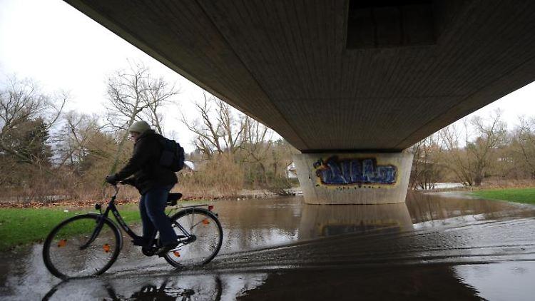 Eine Frau fährt mit ihrem Rad in Melsungen über einen von der Fulda überfluteten Radweg. Foto: Uwe Zucchi/Archiv
