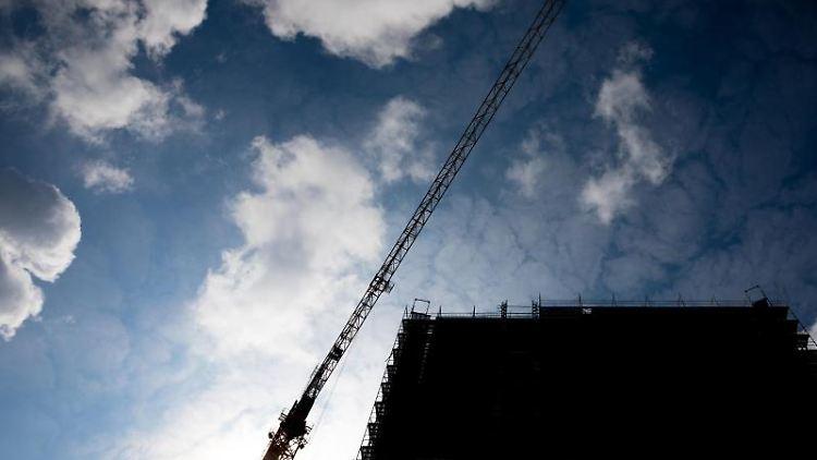 Wolken ziehen über einen Baukran und einem im Rohbau befindliches Gebäude hinweg. Foto: Moritz Frankenberg/Archiv