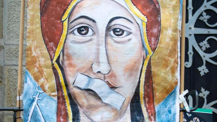 Ein Transparent zeigt Maria, die Mutter Gottes, mit einem Pflaster auf dem Mund anlässlich. Foto: Friso Gentsch/Archivbild