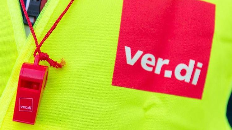 Eine Warnweste mit dem Verdi-Logo und eine rote Trillerpfeife. Foto: Christophe Gateau/Archivbild