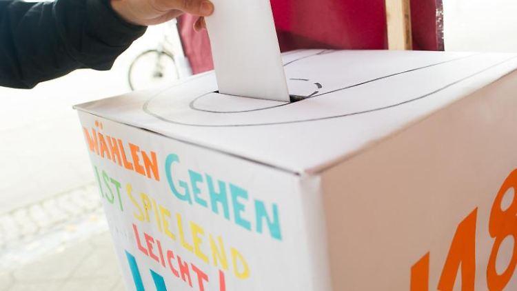 Ein Jugendlicher wirft an einem Wahlstand für die U-18-Wahl einen Wahlzettel in eine Wahlurne. Foto: Klaus-Dietmar Gabbert/Archivbild