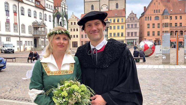 Ramona Weiss als Katharina von Bora und Marco Glaß als Martin Luther stehen in der Innenstadt Wittenbergs nebeneinander. Foto: Johannes Winkelmann