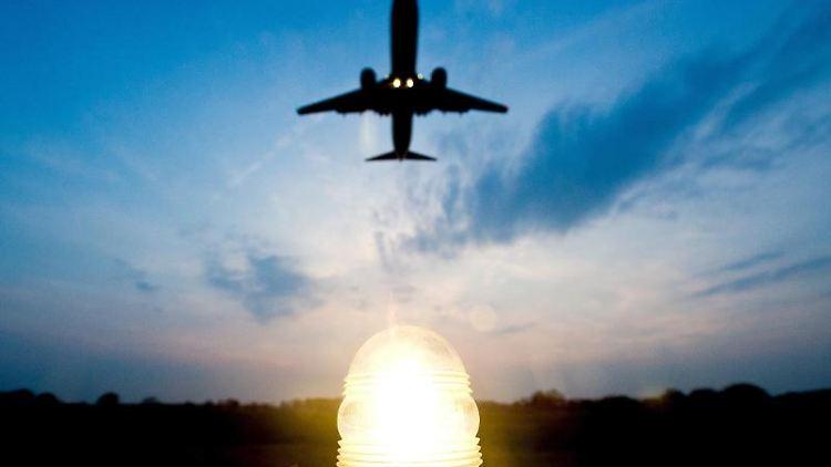 Eine Boeing 737-800 fliegt zur blauen Stunde über die Anflugbefeuerung vom Flughafen. Foto: Christoph Schmidt/Archiv
