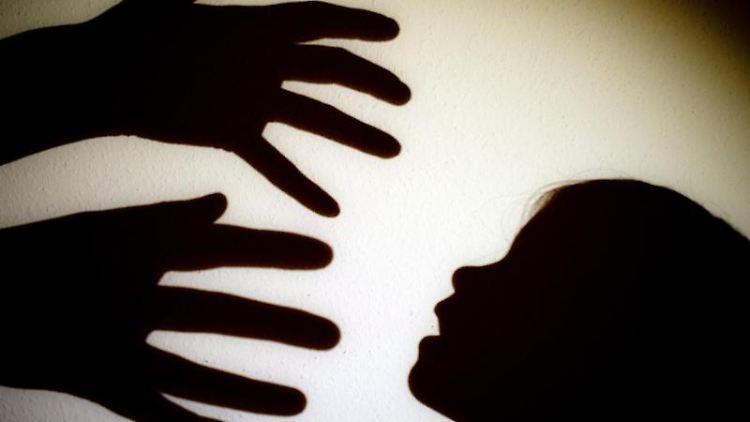 Schatten von Händen einer erwachsenen Person und dem Kopf eines Kindes an einer Wand eines Zimmers. Foto: Patrick Pleul/Archiv