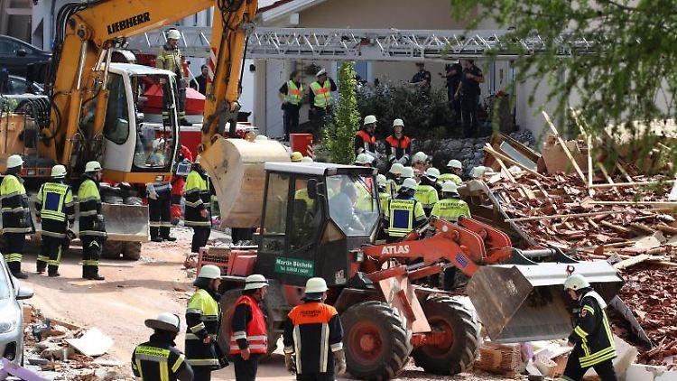 Einsatzkräfte räumen an einem zerstörten Haus Schutt beiseite. Foto: Karl-Josef Hildenbrand