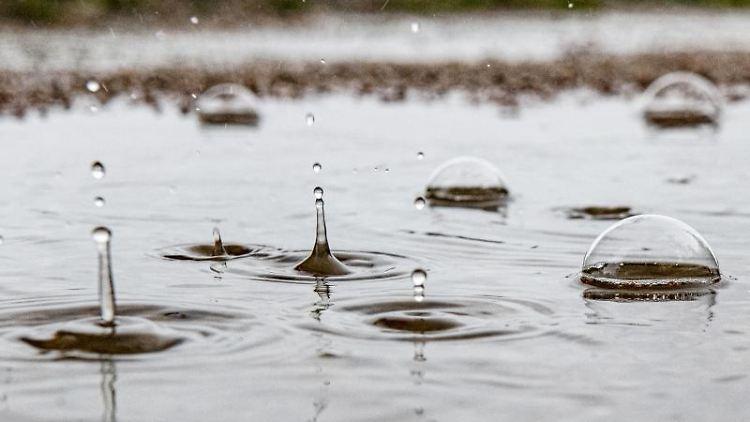 Regentropfen fallen in eine Pfütze und erzeugen durch den Aufprall kunstvolle Gebilde. Foto: Paul Zinken/Archivbild