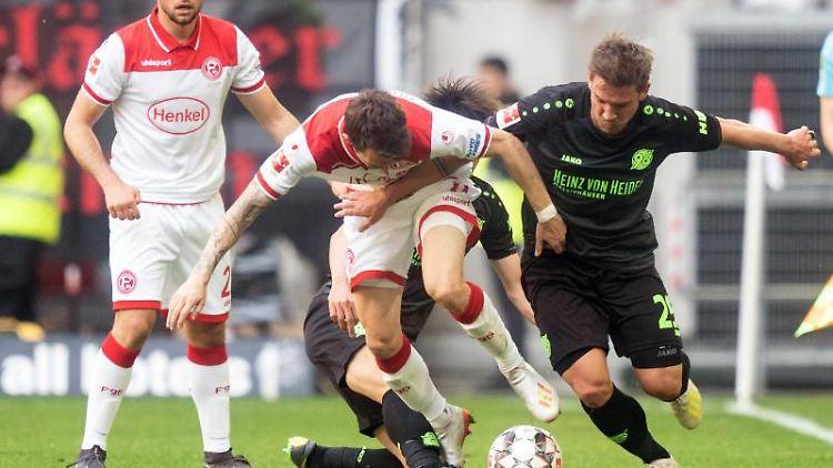 Benito Raman (M) und Oliver Sorg versuchen an den Ball zu kommen. Kevin Stöger aus Düsseldorf (l) schaut zu. Foto: Bernd Thissen