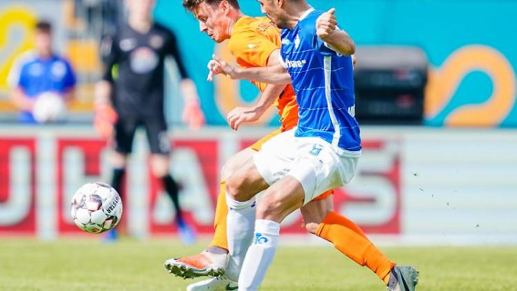 Clemens Fandrich (l.) von Erzgebirge Aue und Darmstadts Slobodan Medojevic kämpfen um den Ball. Foto: Uwe Anspach