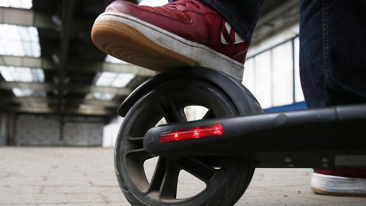 Ein Mann tritt auf einem Testgelände die Bremse eines Elektro-Rollers (E-Scooter). Foto: Oliver Berg/Archivbild