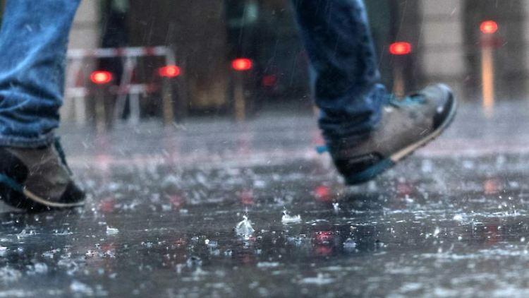 Ein Mann geht im Regen über die Straße. Foto: Paul Zinken