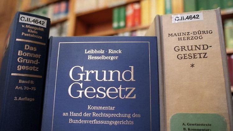 Verschiedene Ausgaben des Gundgesetzes und Kommentare dazu im Lesesaal einer Bibliothek. Foto: Kalaene Jens/Archivbild