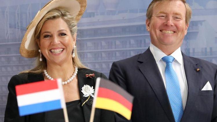 Das niederländische Königspaar Willem-Alexander und Maxima steht hinter einem niederländischen und deutschen Fähnchen. Foto: Bernd Wüstneck