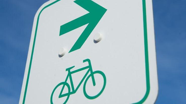 Ein Fahrrad und ein Pfeil sind auf einem Schild zu sehen. Foto: Stefan Sauer/Archivbild