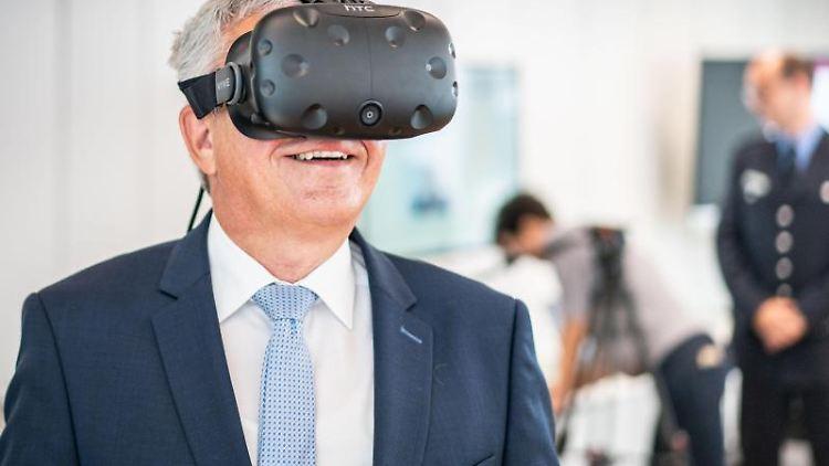 Roger Lewentz (SPD), Innenminister von Rheinland-Pfalz, trägt eine VR-Brille. Foto: Frank Rumpenhorst