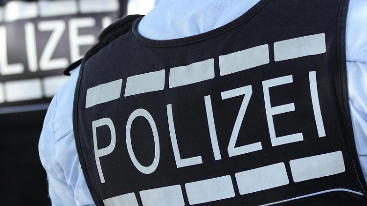 In Polizei-Westen gekleidete Polizisten stehen mit dem Rücken zur Kamera. Foto: Silas Stein/Archivbild