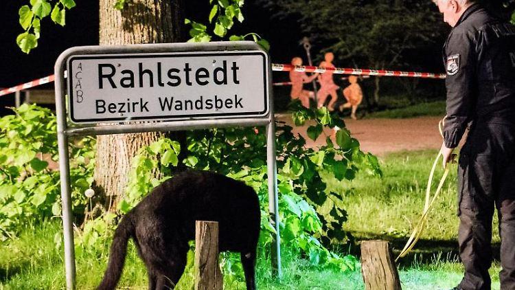Ein Polizist sucht mit einem Hund einen Tatort im Stadtteil Rahlstedt ab. Foto:DanielBockwoldt