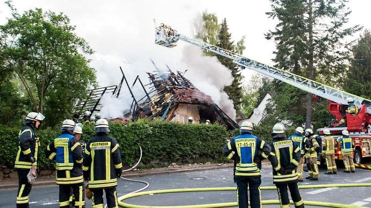 Feuerwehrleute stehen vor den Trümmern eines Wohnhauses, das bei einem Brand zerstört wurde. Foto:Daniel Bockwoldt