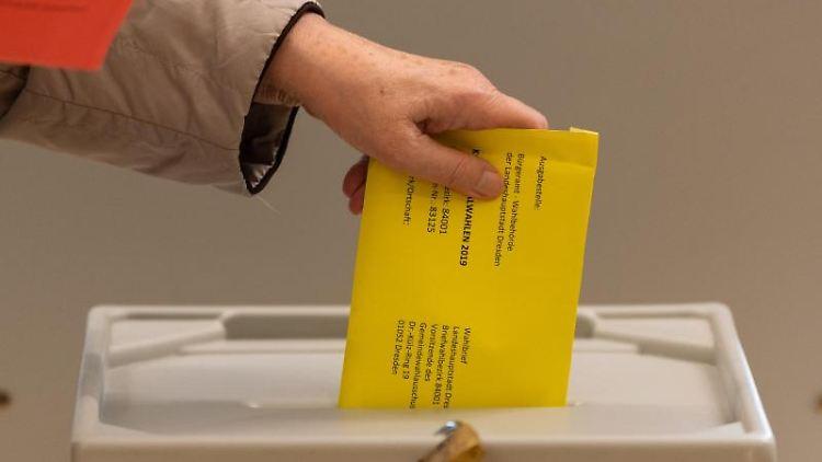Eine Frau wirft im Wahllokal einen Briefumschlag mit dem Stimmzettel in eine Wahlurne. Foto:Robert Michael/Archivbild