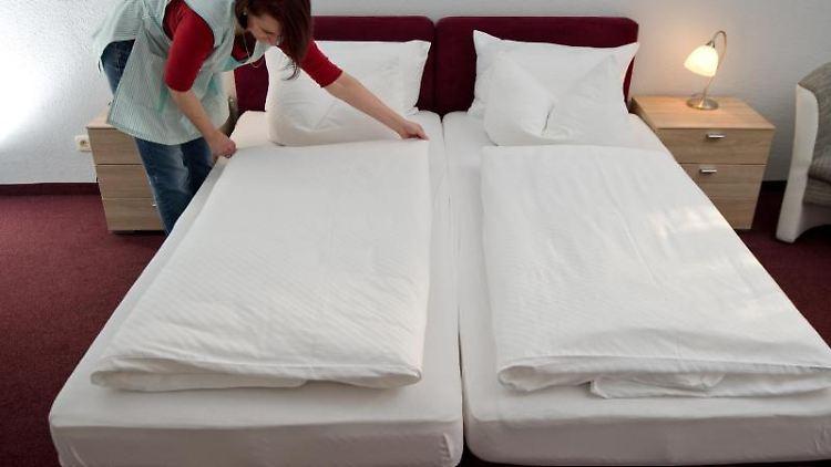 Eine Zimmerfrau macht in einem Gästehaus das Bett. Foto: Swen Pförtner/Archivbild