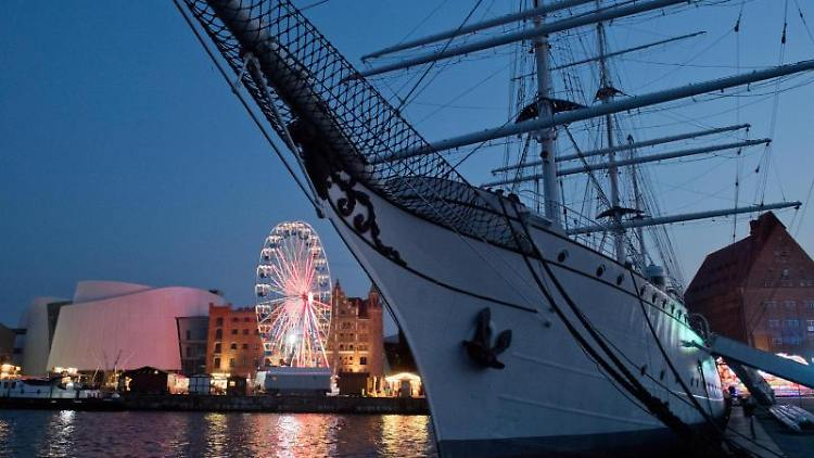 Ein Riesenrad steht im Stralsunder Stadthafen hinter dem Schiff Gorch Fock I. Foto: Stefan Sauer/Archivbild