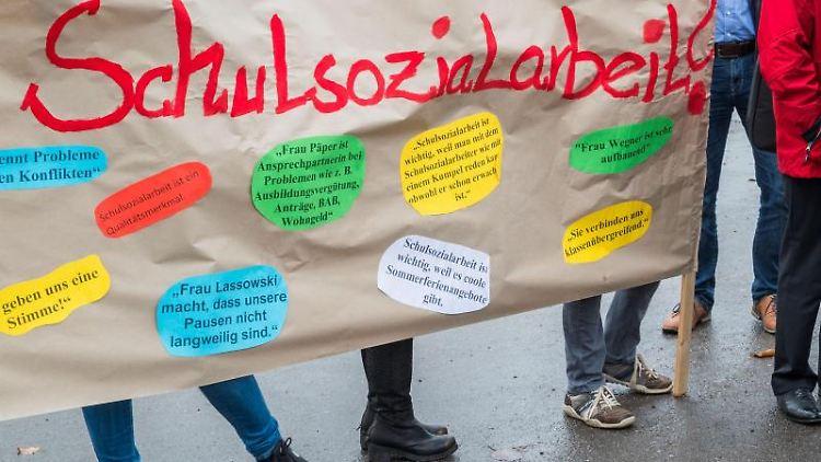 Teilnehmer einer Demonstration halten ein Plakat mit der Aufschrift