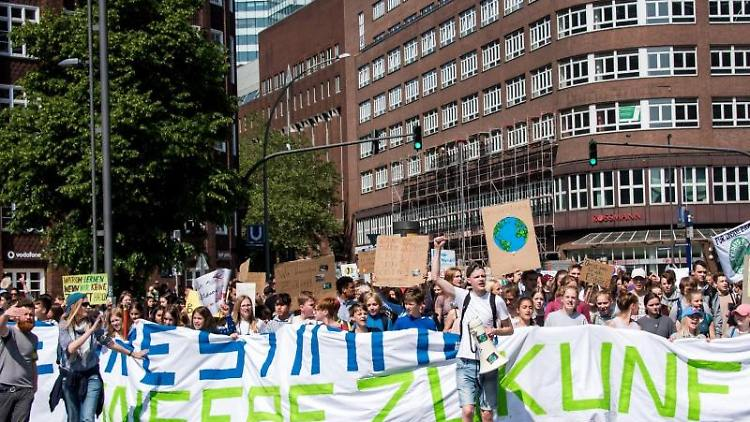 Schülerinnen und Schüler demonstrieren mit Protestplakaten und einem Transparent während des Fridays for Future - Klimastreiks. Foto: Daniel Bockwoldt