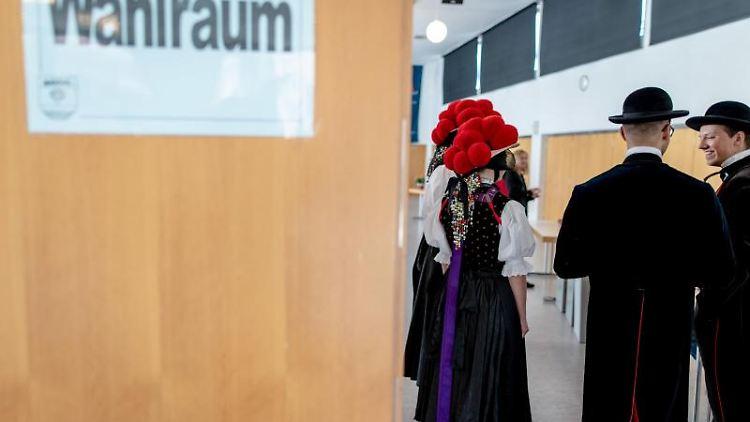 Trachtenträger warten im Wahllokal darauf, dass sie bei der Europawahl ihre Stimmen abgeben können. Foto: Patrick Seeger