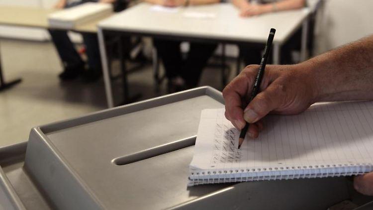 Ein Wahlleiter streicht in einem Wahllokal einen Anstreichzettel zur Ermittlung der Wahlbeteiligung ab. Foto: Christian Charisius/Archivbild