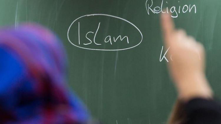 Eine Schülerin mit Kopftuch meldet sich an einer Schule bei einer Unterrichtsstunde zum Thema Islam. Foto: Frank Rumpenhorst/Archivbild