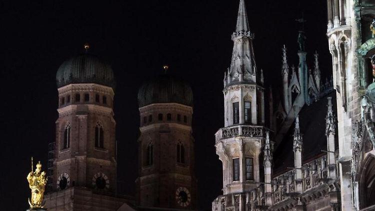 Die Bildkombo zeigt die Frauenkirche und das Rathaus in München beleuchtet und unbeleuchtet. Foto: Matthias Balk/Archiv