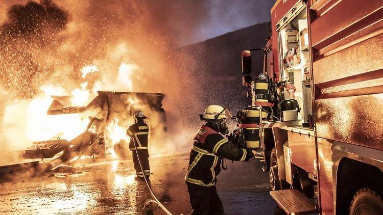 Feuerwehrleute löschen in Reichenbach bei Idar-Oberstein den Brand auf einer Mülldeponie. Foto:Christian Schulz