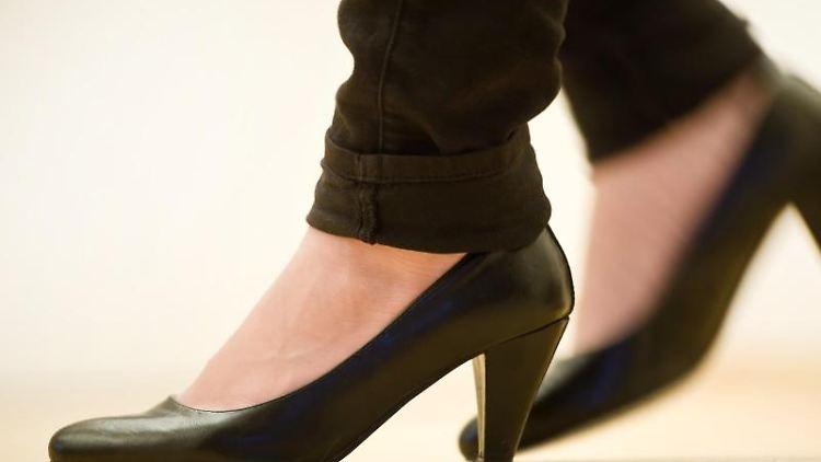 Eine Frau läuft mit hohen Schuhen über einen Parkettboden. Foto: Daniel Naupold/Archivbild