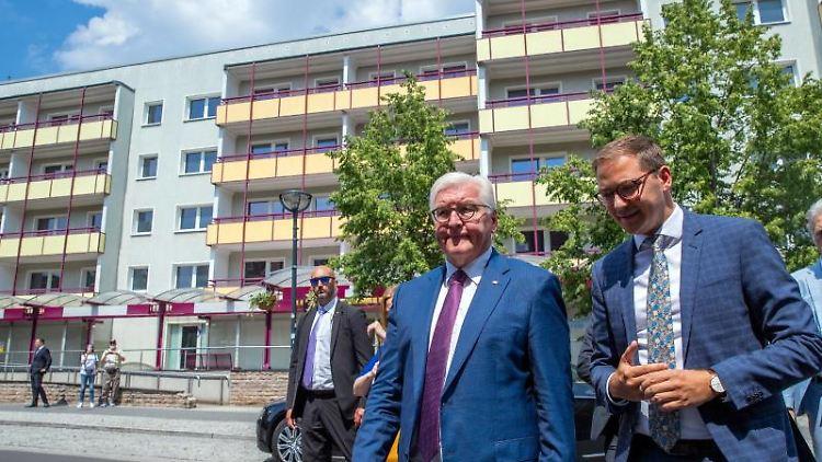 Bundespräsident Frank-Walter Steinmeier geht mit Patrick Dahlemann (SPD), Staatssekretär, an leeren Wohnblocks vorbei. Foto:Jens Büttner