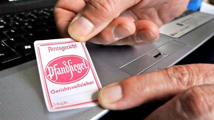 Ein Pfandsiegel wird auf einen Laptop geklebt. Foto: Georg-Stefan Russew/Archiv