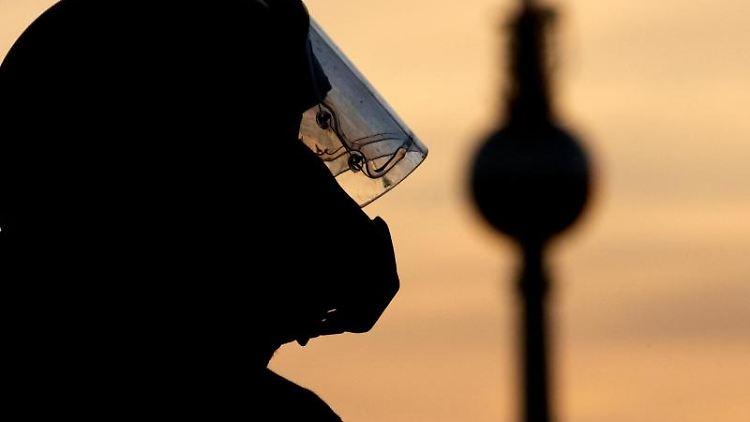 Die Silhouette eines Polizisten ist vor dem Abendhimmel zu sehen. Foto: Ralf Hirschberger/Archivbild