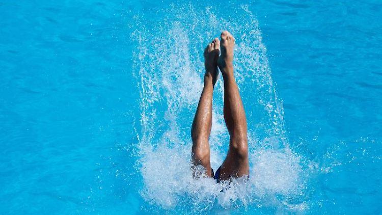 Ein junger Mann landet nach einem Sprung vom Drei-Meter-Brett im Kaifu-Bad im Wasser. Foto: Daniel Reinhardt/Archivbild
