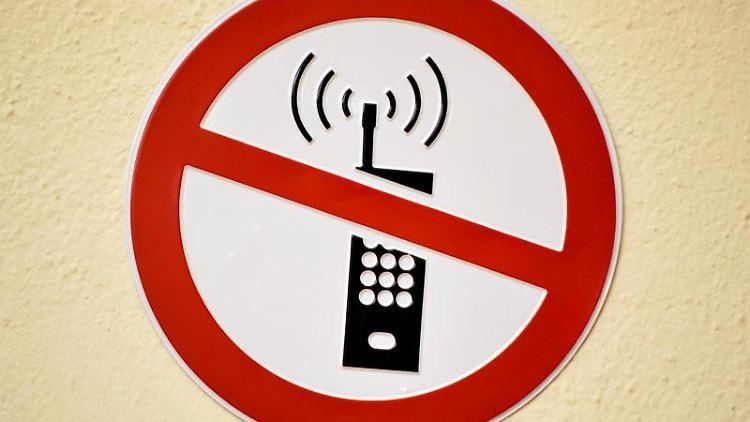 Ein Schild weist auf eine Verbot für Mobiltelefone hin. Foto: Arne Dedert/Archivbild