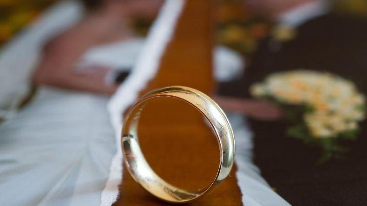 Auf einem Tisch liegt ein zerrissenes Hochzeitsfoto und ein Ehering. Foto: Patrick Pleul/Archivbild