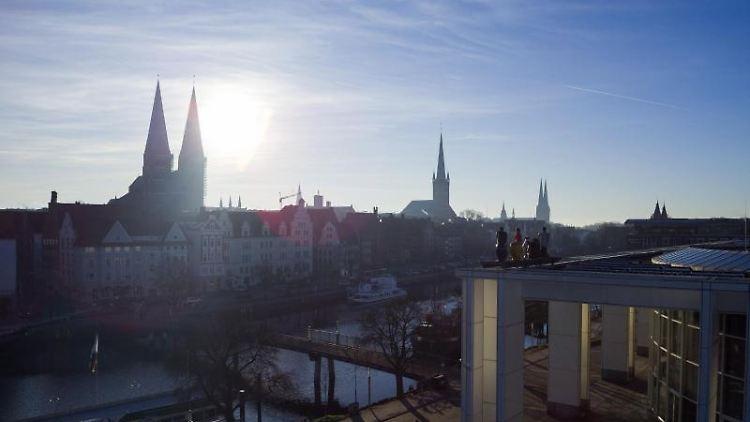 Die Sonne geht über Lübeck auf. Foto: Rainer Jensen/Archiv
