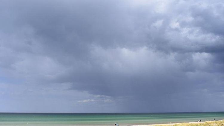 Dunkle Wolken ziehen an der Ostsee über das Meer. Foto:Stefan Sauer/Archivbild