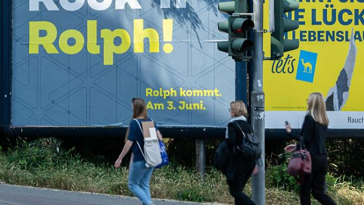 Frauen gehen an einem Plakat mit der Aufschrift