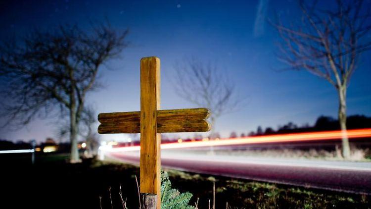 Ein Kreuz zur Erinnerung an einen Verkehrstoten steht an einer Landstraße. Foto: Julian Stratenschulte/Archivbild