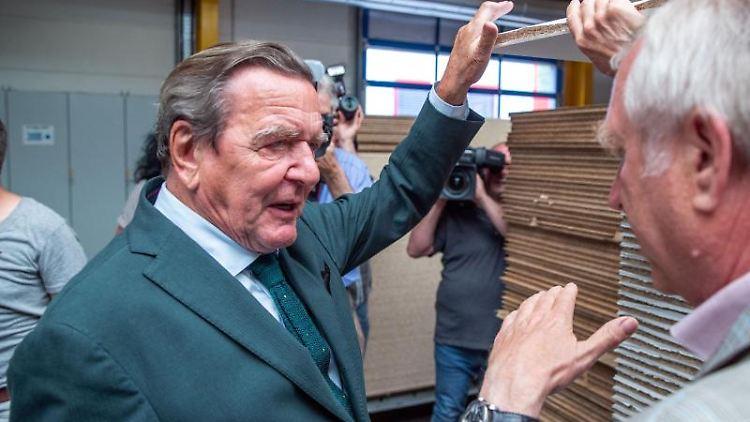 Der Ex-Bundeskanzler Gerhard Schröder (SPD, l) spricht mit dem Geschäftsführer des Meyenburger Möbelwerks, Dietmar Gornig. Foto:Jens Büttner