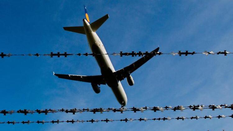 Ein Flugzeug ist am Flughafen hinter Stacheldraht zu sehen. Foto: Julian Stratenschulte/Archivbild