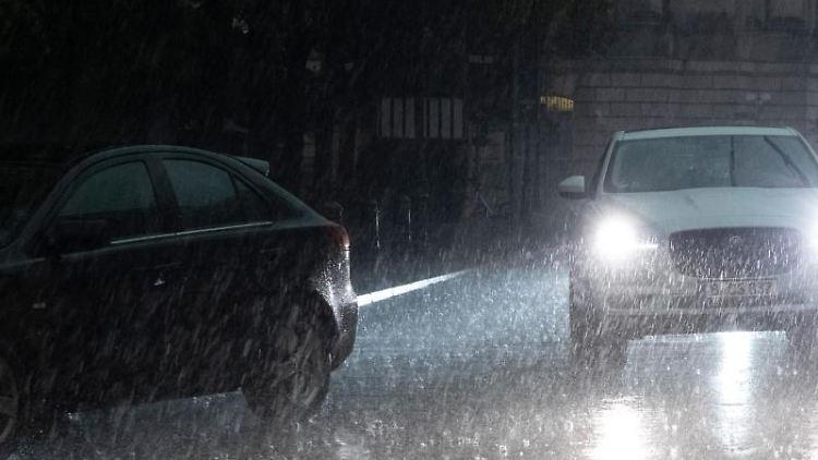 EinFahrzeug fährt in Berlin bei Regen über die Straße. Foto: Paul Zinken