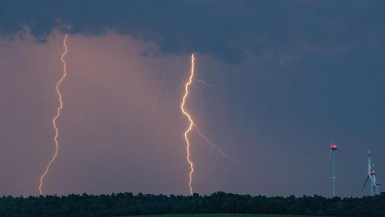 Blitze eines Gewitters erhellen den Abendhimmel über der Landschaft. Foto:Patrick Pleul