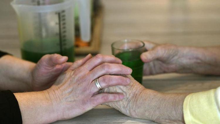 Eine Betreuerin fasst die Hände einer demenzkranken Frau in der ersten Demenz-WG an. Foto:Ina Fassbender/Archivbild