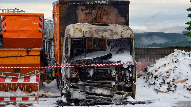 Ein verbrannter Lkw steht, bedeckt von Löschschaum, neben einem Container einer Recyclingfirma. Foto:AndreasRosar/Fotoagentur Stuttgart/dpa