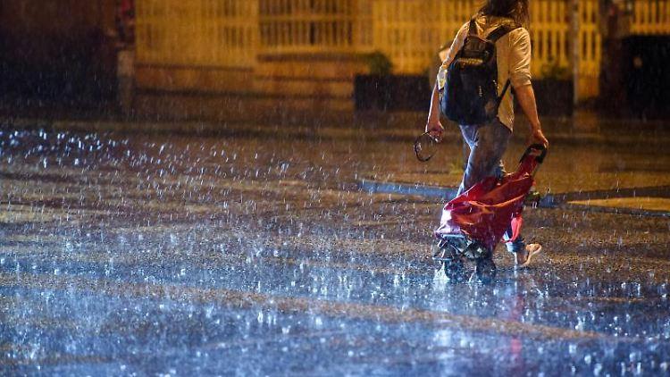 Ein Mann zieht bei starkem Regen während eines Sommergewitters einen Einkaufswagen hinter sich her. Foto: G. Fischer/dpa/Archiv