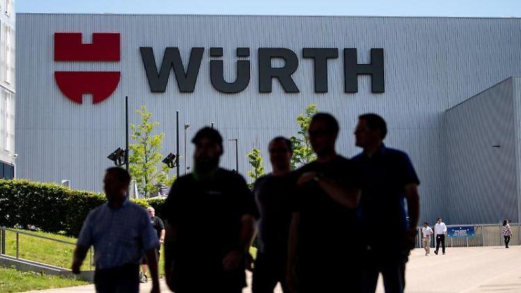 Mitarbeiter des Handelskonzern Würth stehen vor dem Logo des Unternehmens. Foto: Fabian Sommer/Archivbild